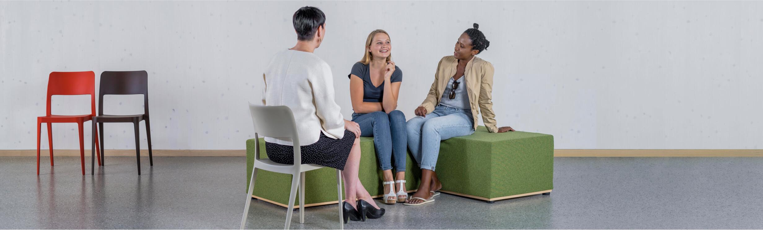 Drei Frauen sitzen beisammen und unterhalten sich