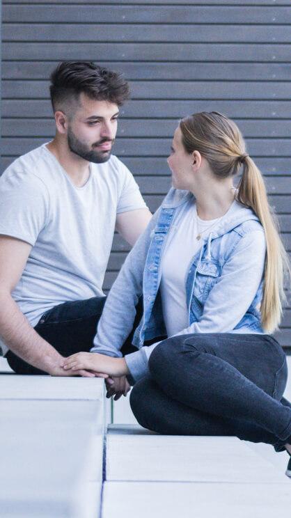 Ein junger Mann und eine junge Frau sitzen auf einer Treppe und schauen sich an